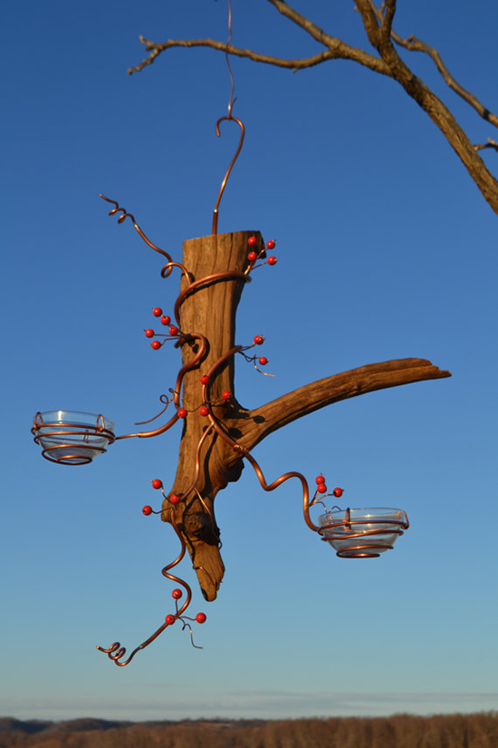 Bird feeders made of small glass pots hanging on a tree