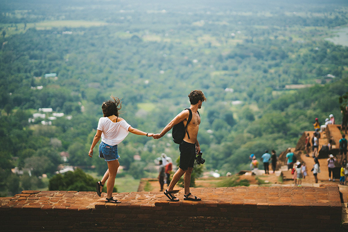 Couple holding hands and walking on a wall while looking at the good nature in front