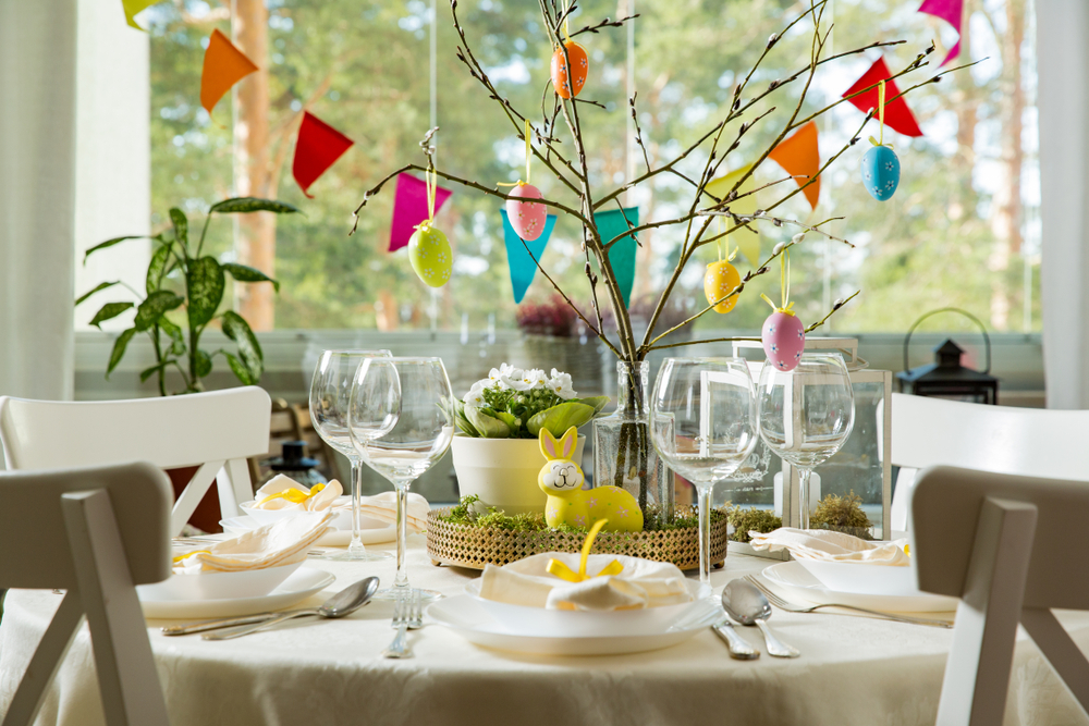 Tree branches with Easter eggs hanging and a plastic bunny in front of it put on a table