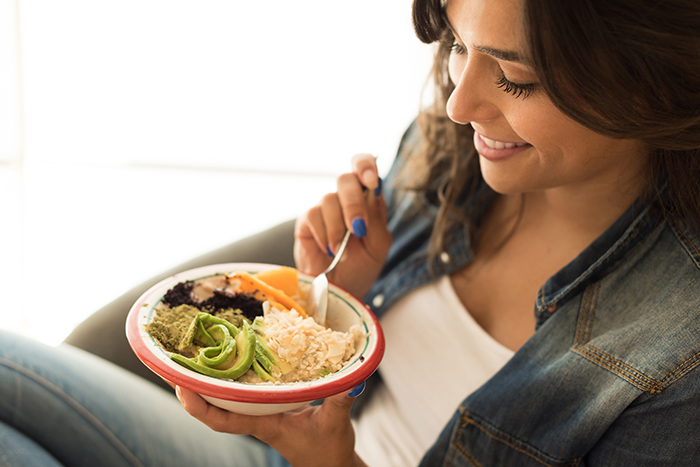 Smiling woman eating a healthy meal