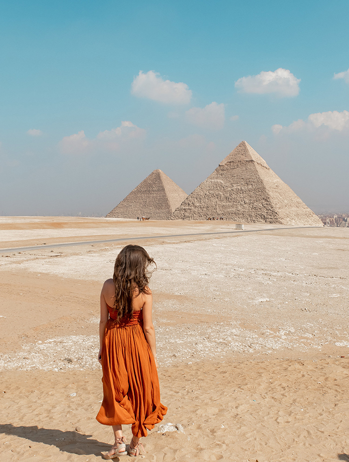 Woman in a dress turned with the back looking at the pyramids