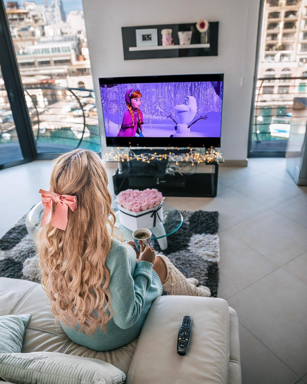 Girl with a bow in her hair watching animated movie in a modern living room