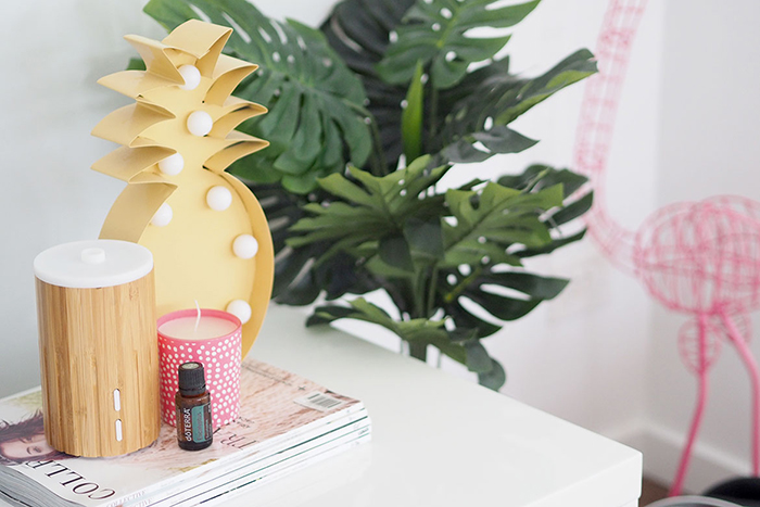 Wooden essential oil diffuser for home use with pink candle next to it