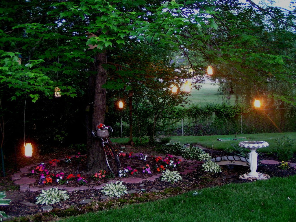 Yard surrounded with flowers and a big trees with candles in jars hanging on it