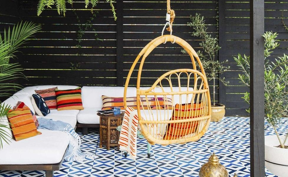 Hanging Arch Chair swing placed in a nice living room with colorful cushions on the bed behind