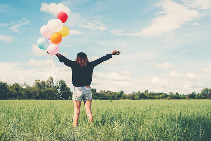 Woman with balloons in a meadow