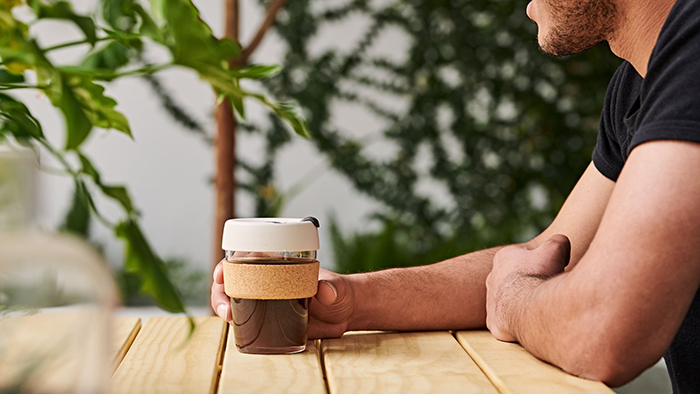 Man sitting and drinking coffee from reusable cup