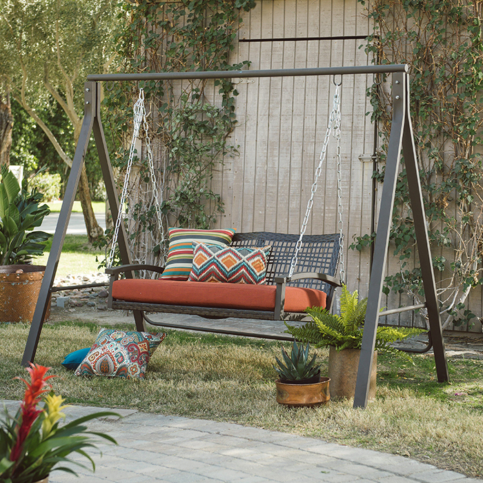 Outdoor metal porch swing with colorful cushions on it