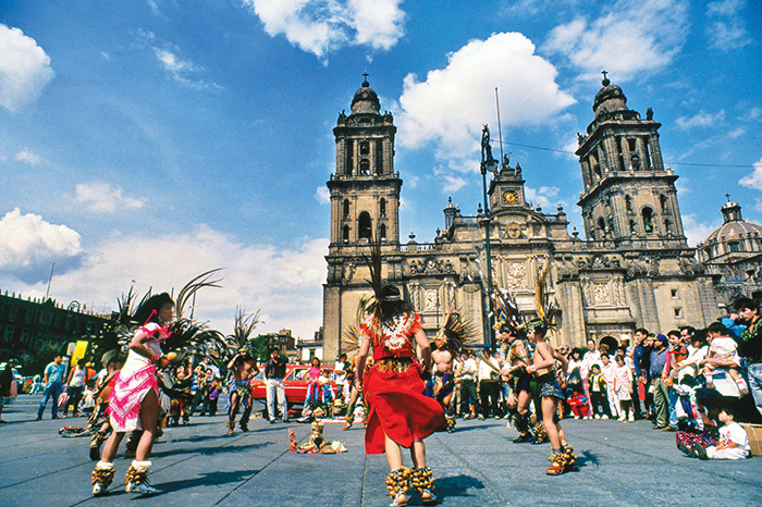 People in traditional clothes dancing in front of a cathedral in Mexico