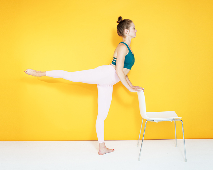 Girl doing exercises with the help of a chair