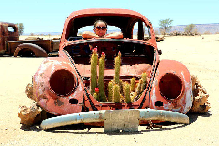 Woman sitting in an old classic car with cactus growing in it