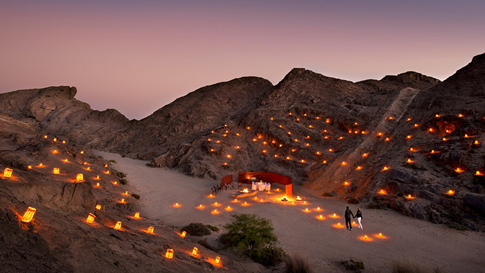 Romantic candles around the small hills and a couple reaching their dinner table