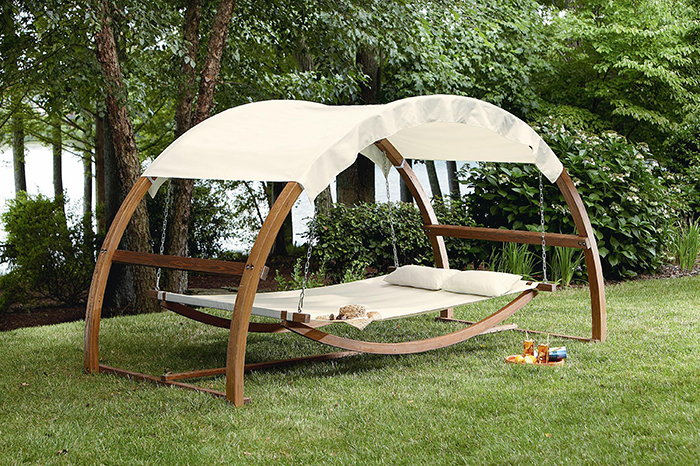 Swing with canopy placed at the patio and surrounded with good nature