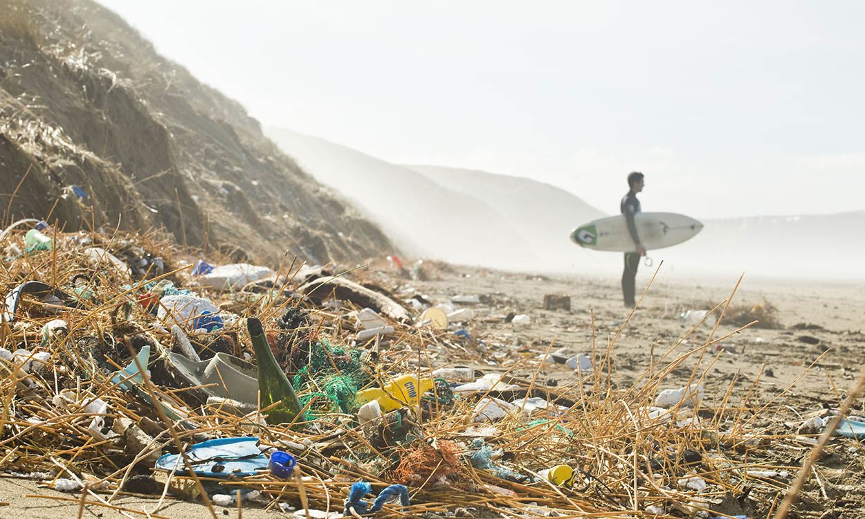 Polluted beach with plastic and a surfer
