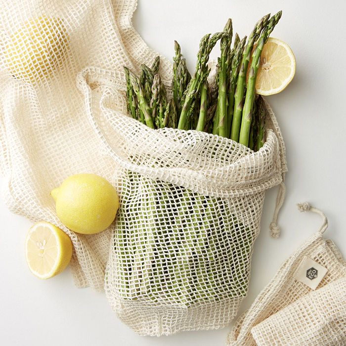 Reusable grocery bag filled with asparagus and lemon