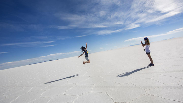 Girl jumping and another one taking a picture of her in a salt flat