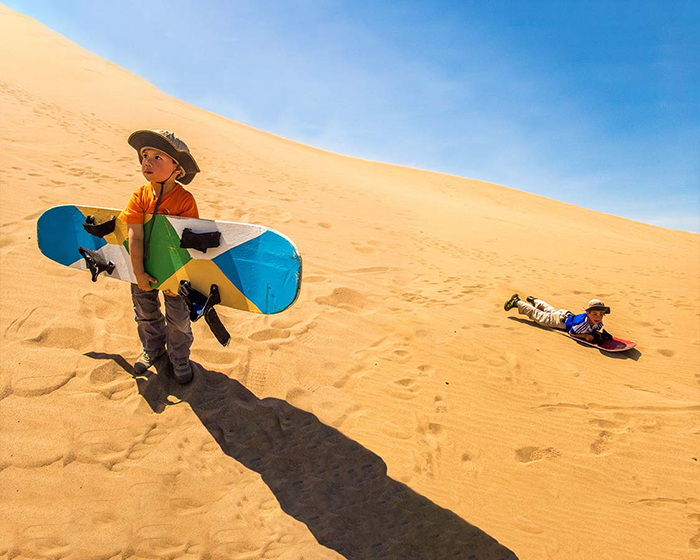 Kids sand boarding though the red dunes