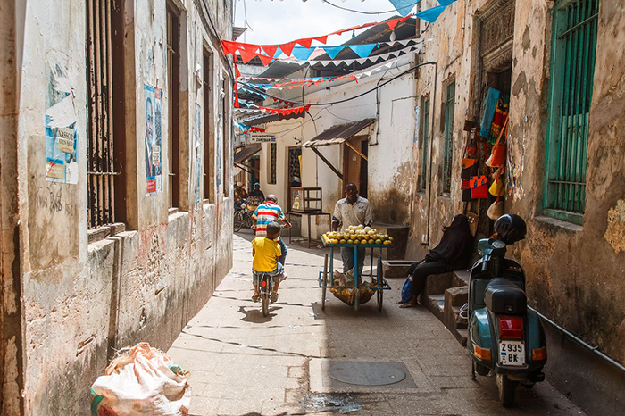 Small street in Stone Town with kids on a bike and a street vendor