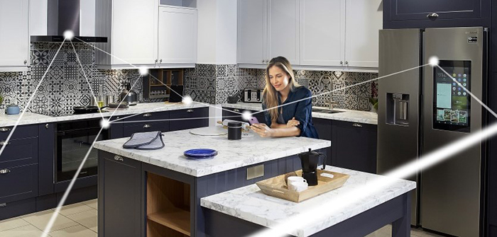 Woman standing in a smart kitchen and controlling the cooking process through her smartphone