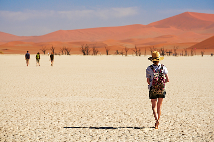 Girl with a hat and a bag walking through a desert
