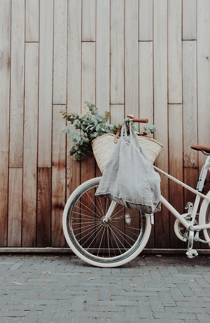 Vintage bike put near to a wooden wall and sustainable grocery bag on it