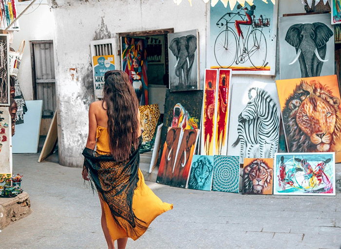 Woman wandering around Stone Town and an art house next to her