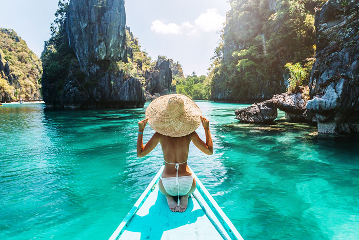Woman on a small boat around the clean waters and rocks in The Philippines
