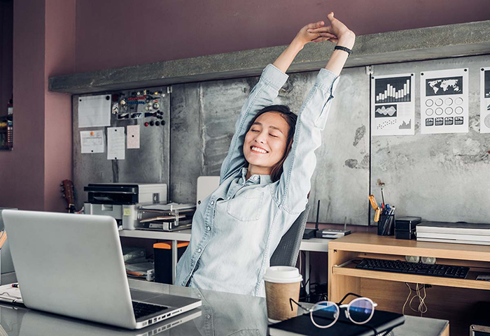 Woman stretching at her work place with closed eyes