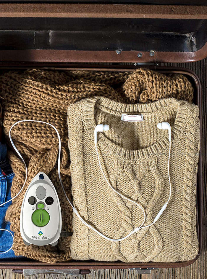 Luggage with mini iron travel steam, brown sweater and headphones