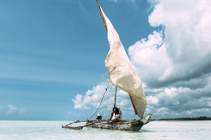 Woman enjoying the sun on a wooden boat