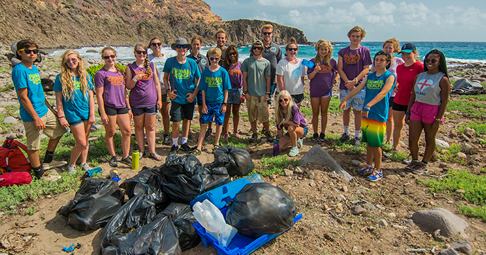 Young volunteers cleaning the beach from plastic