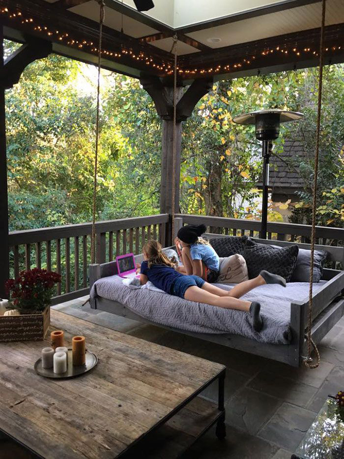 Two girls chilling at their wooden porch in the house balcony
