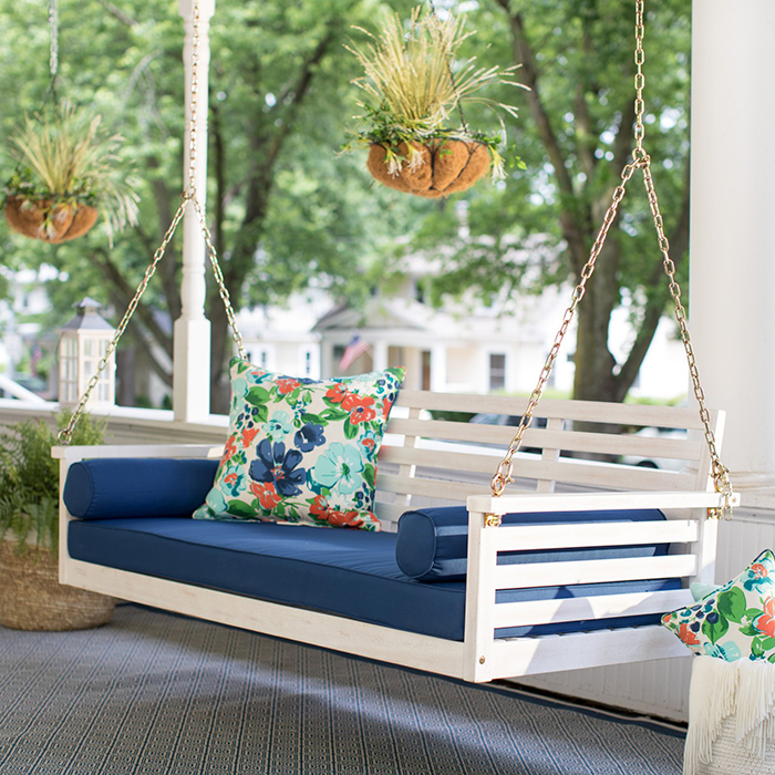 Wooden porch swing with floral cushions