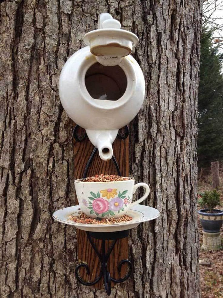 Bird feeder made of tea kettle and a tea cup hanging on a tree