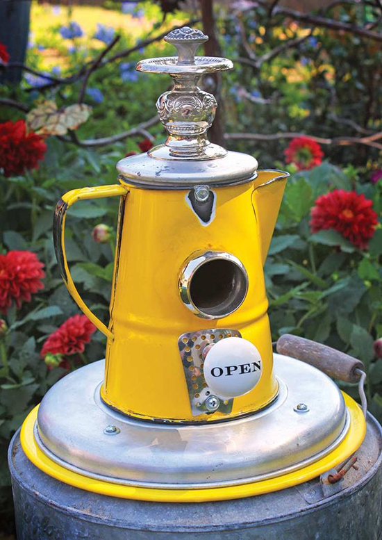 Bird house in a big old kettle with nice flowers in the background