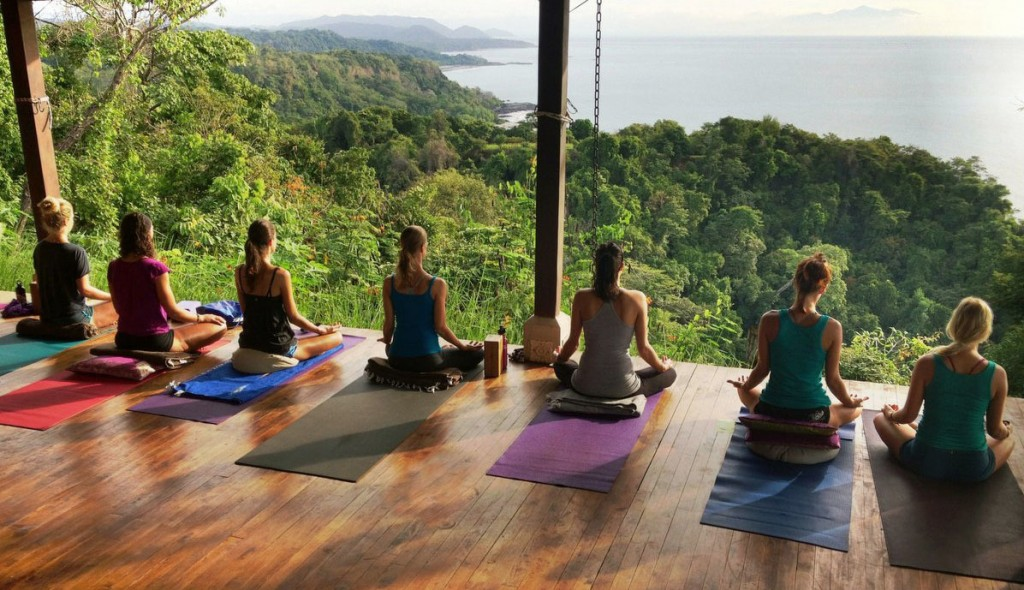 Women doing yoga in a resort with a forest and sea view