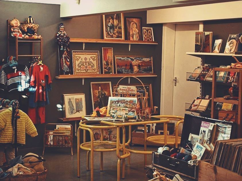 Second-hand shop full of vintage pictures, books, kids' clothes and a table in the middle