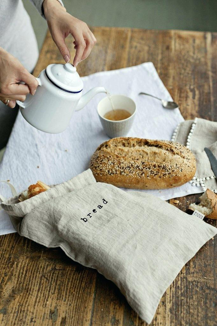 Linen bread bag on a table and a woman sipping tea