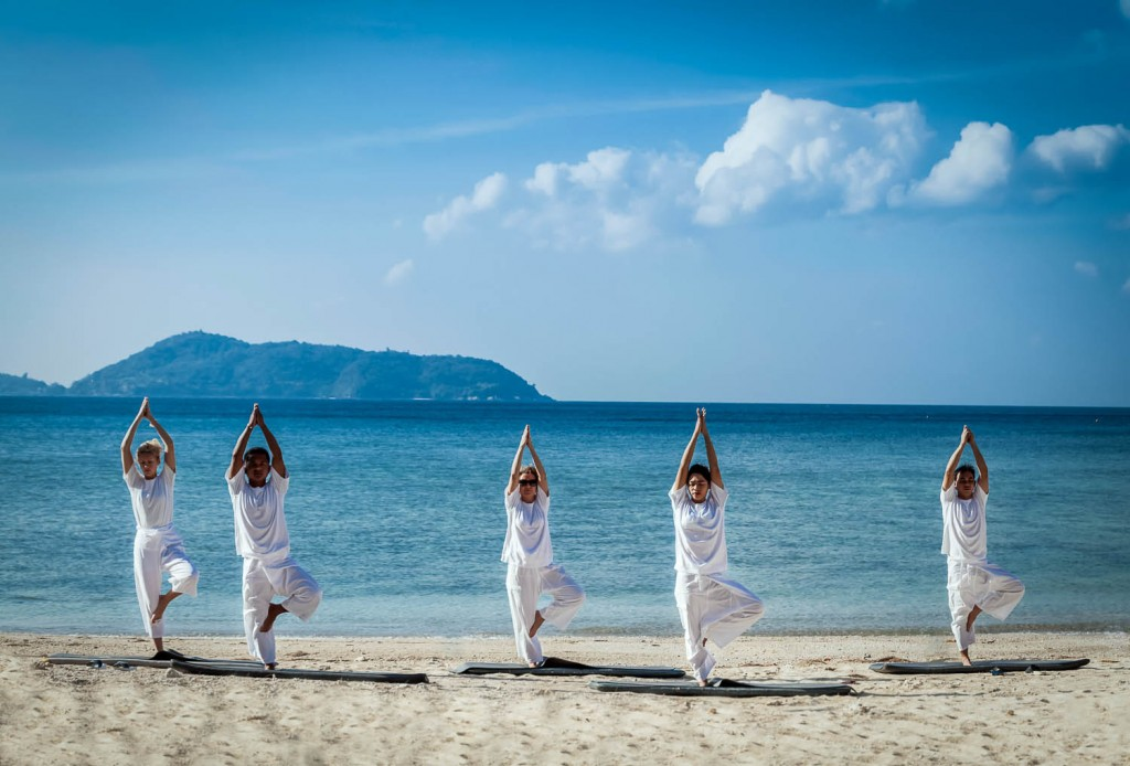 People practicing yoga on open air with an ocean view