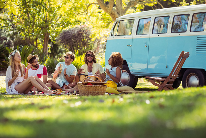 Group of friends having picnic in a meadow and their retro bus behind them