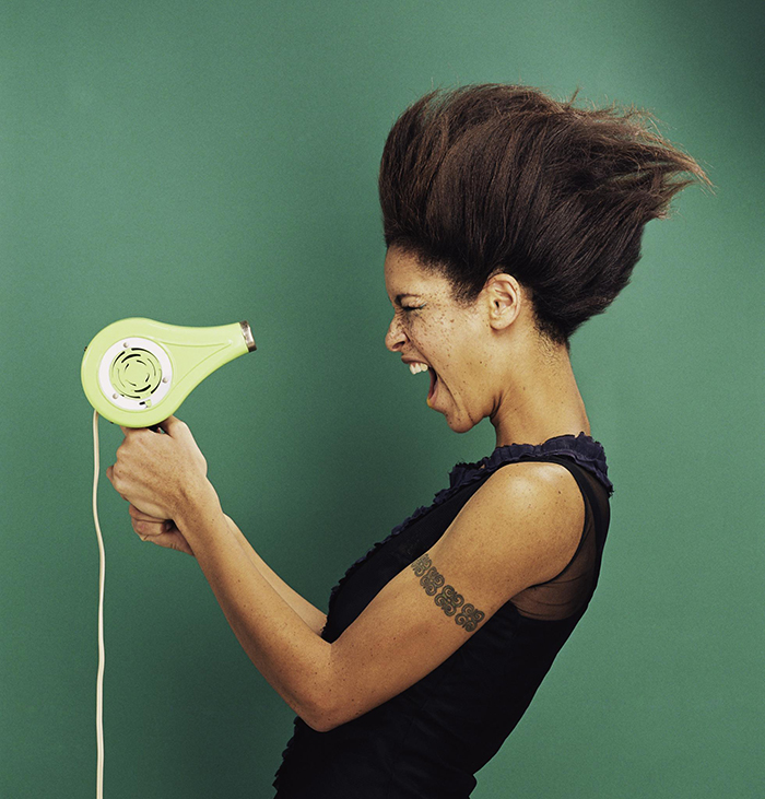 Woman with green hair dryer blowing her hair hair care tips
