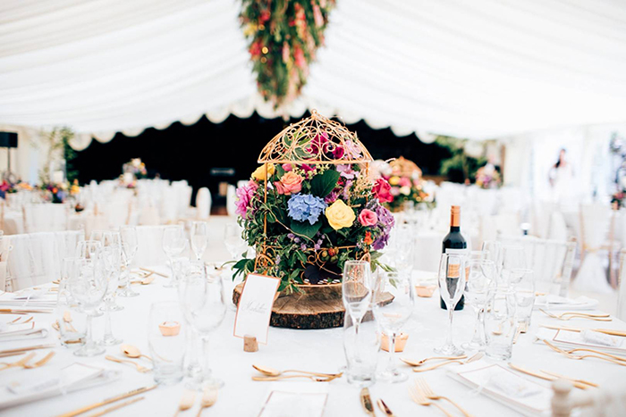 Different kind of flowers on the wedding table accompanied with a bottle of wine and glasses