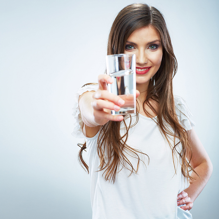 Beautiful woman with long hair with water in her hand