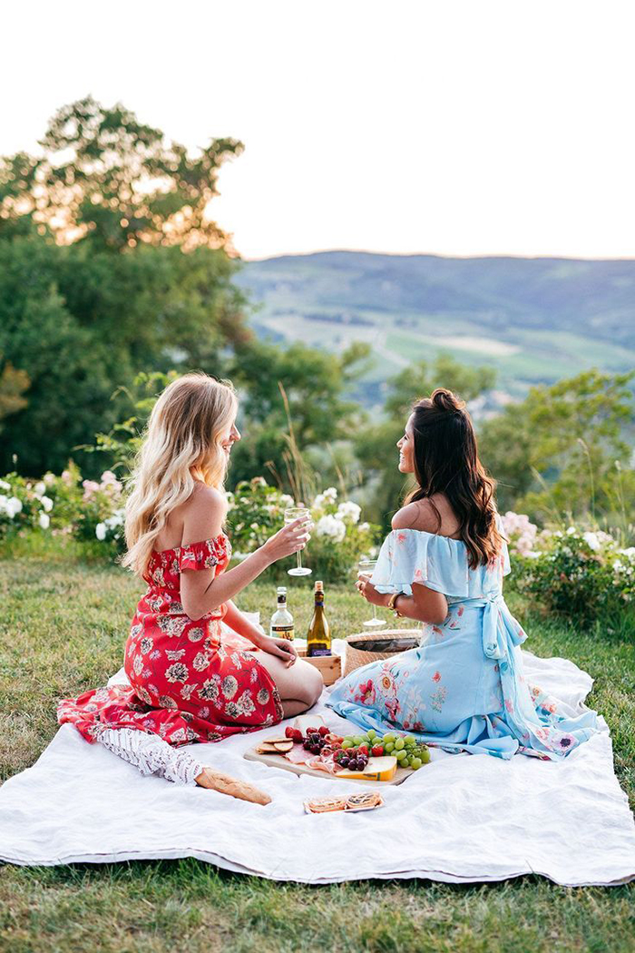 Two girls in dresses enjoying a glass of wine while doing picnic