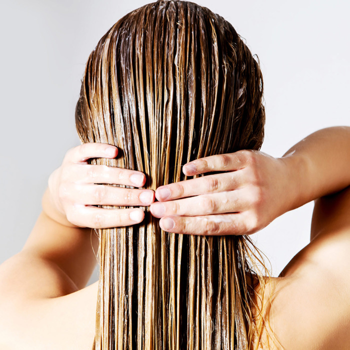 Woman puts hair oil on her blonde hair