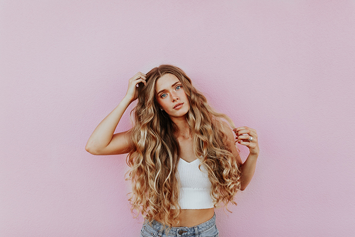 Blonde woman with long curly hair standing in front of pink wall