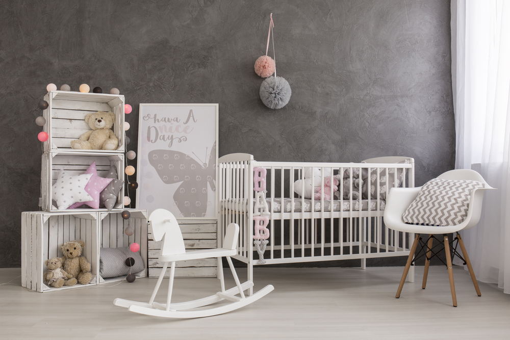 Nursery room in grey shades with cute furnitures in white
