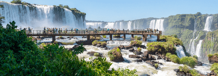 Tourists walking on a small bridge around the Iguazu Falls