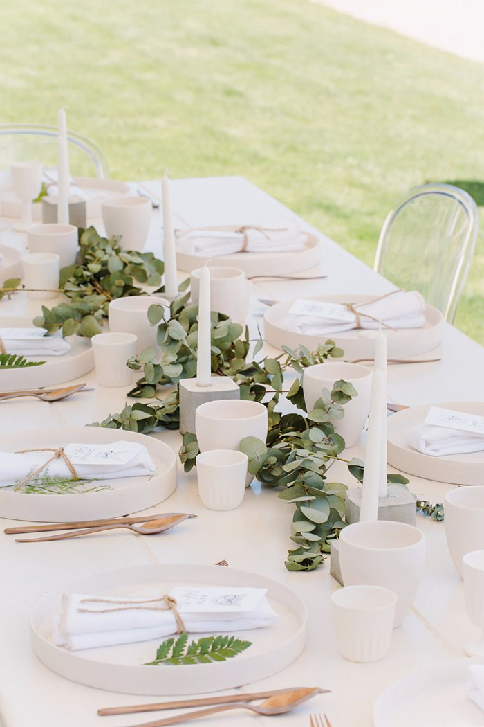 Candles with leaves around them on the wedding table