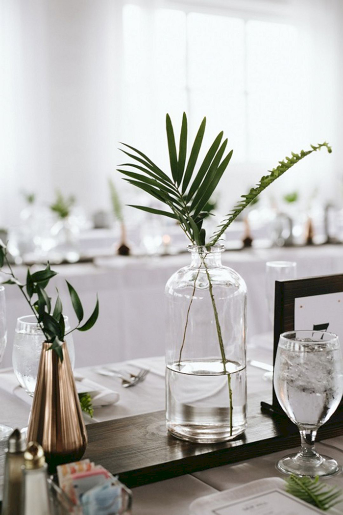 Minimalist table decor with vases filled with leave flowers